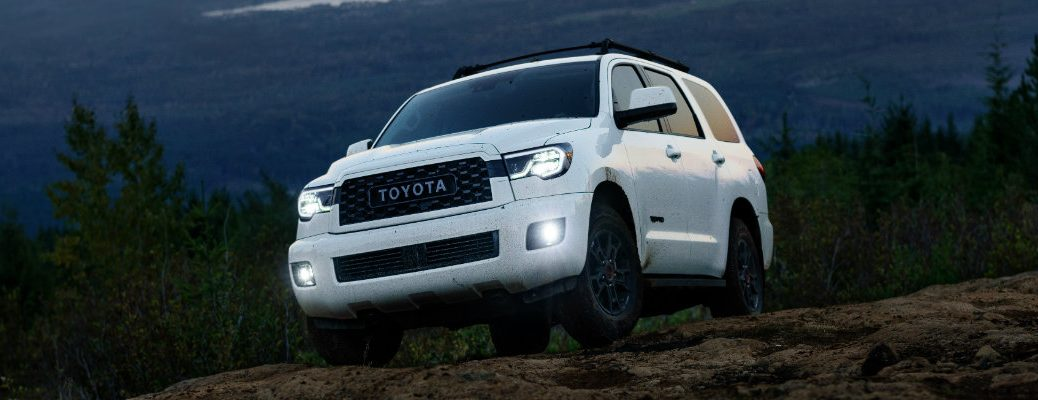 2020 Toyota Sequoia TRD Pro exterior shot with white paint color driving on rocky mountain terrain near forests in the very early morning as the sun rises