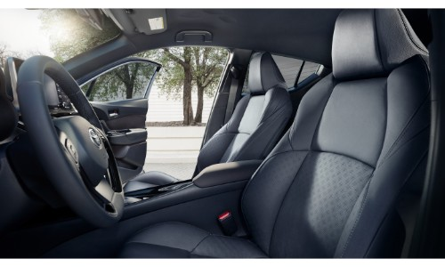 2019 Toyota C-HR interior side shot of front seating upholstery with an outside shot of a white brick building and trees