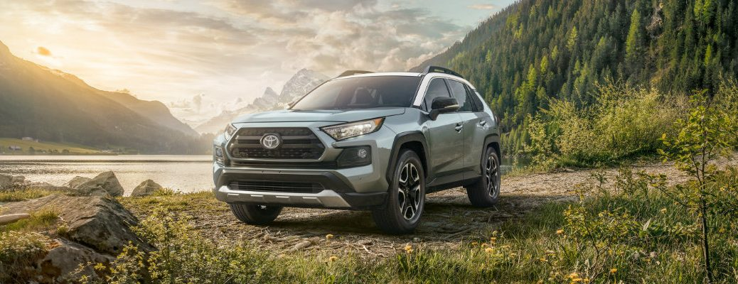 2019 Toyota RAV4 exterior shot with gray paint color parked at the edge of a lake near forest hills, a mountain range, and a rising sun