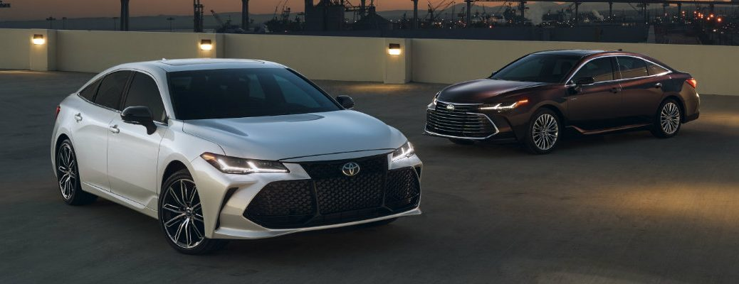 2019 Toyota Avalon with silver paint color and 2019 Toyota Avalon Hybrid with dark red paint color parked outside near an oil drilling station