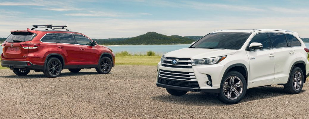 2019 Toyota Highalnder and 2019 Toyota Highlander Hybrid models exterior shot in red and white paint color parked on a gravel lot near grass and the ocean
