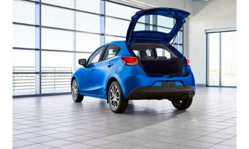 2020 Toyota Yaris Hatchback exterior rear shot with blue paint color and back hatch open while parked in a clean white garage