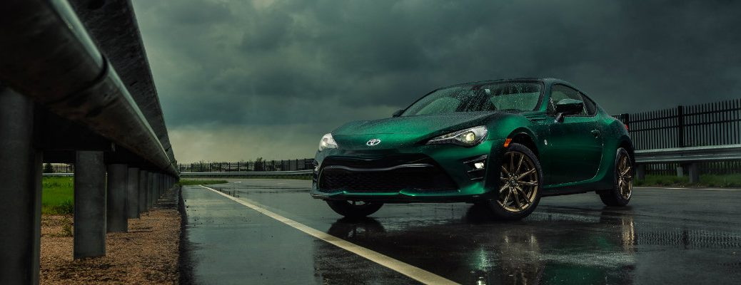 2020 Toyota 86 Hakone Edition exterior shot with exclusive green paint color parked on a race track under raining clouds