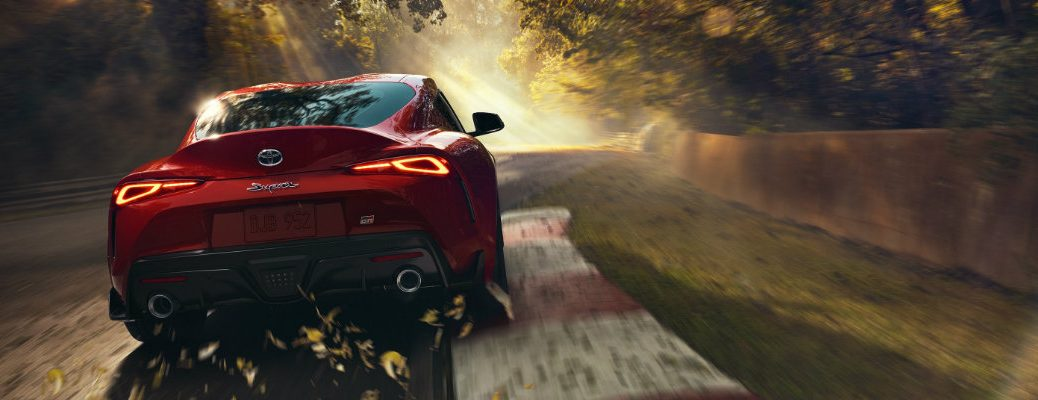 2020 Toyota GR Supra exterior rear shot with renaissance red paint color driving down a race track through a forest