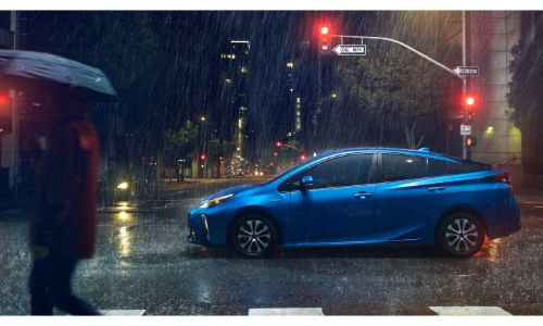 2019 Toyota Prius exterior side shot with blue paint color driving through a city under heavy rain near a lit up streetlight