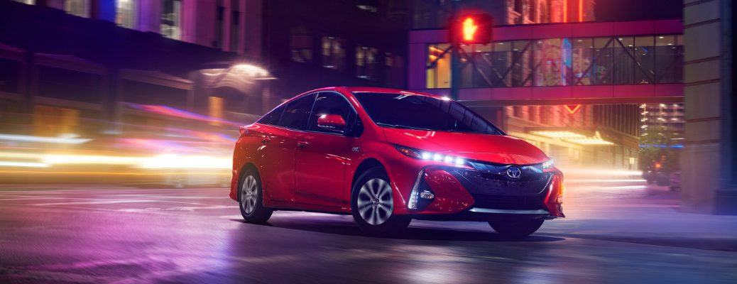 2020 Toyota Prius Prime exterior shot with Supersonic Red paint color driving through a city lit up by neon and blurring lights