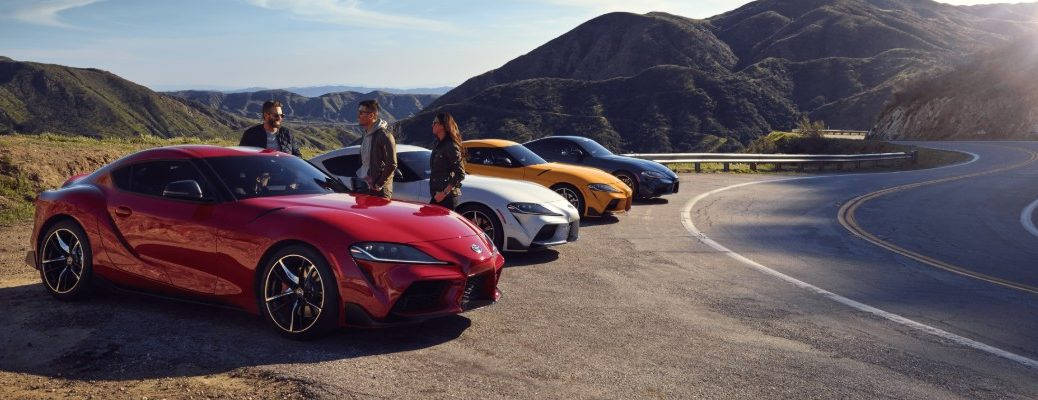 red, white, yellow, and blue 2020 Toyota GR Supra models parked on the side of a country highway as a group of friends inspect the vehicles