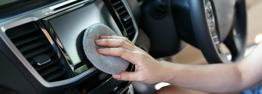 Woman cleaning car's sound system