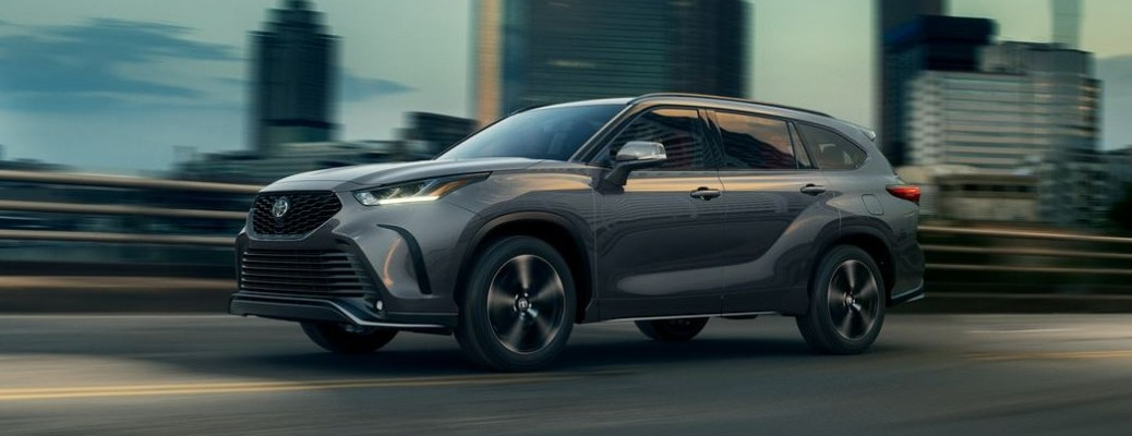 2021 Toyota Highlander driving down a road with a city landscape in the background