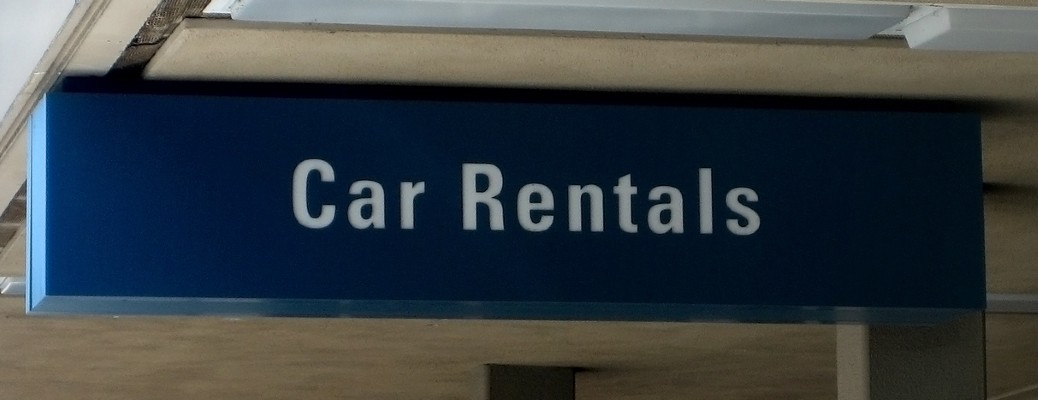 A blue signing hanging that reads Car Rentals