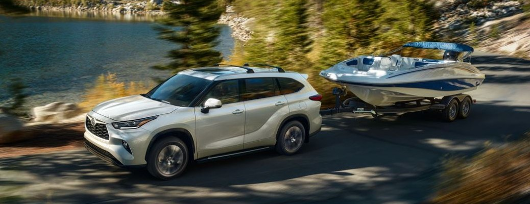 2021 Toyota Highlander towing a boat past a body of water