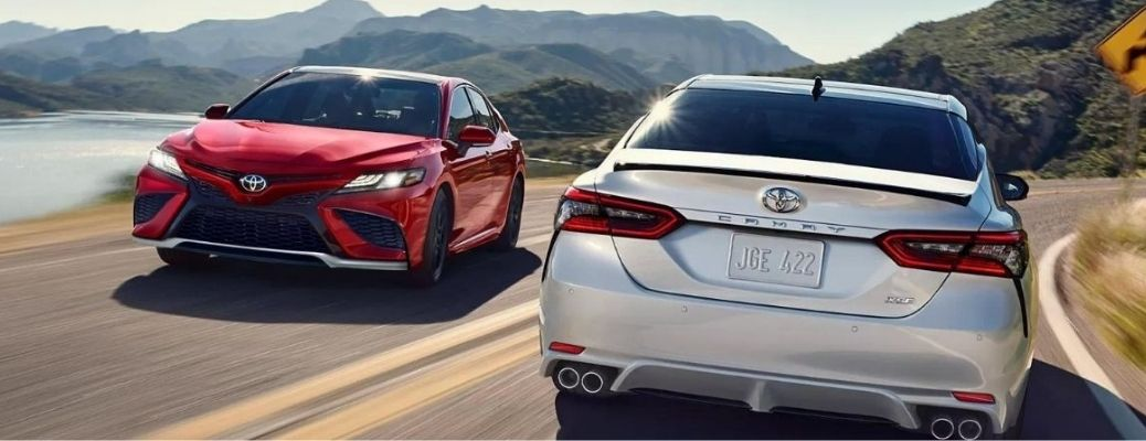 Two 2022 Toyota Camry driving on the road in opposite directions.