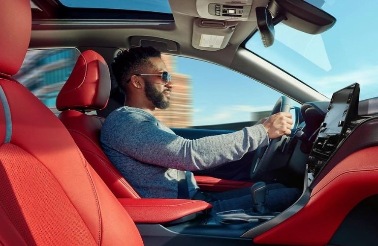 Side view of a man driving of the 2022 Toyota Camry.