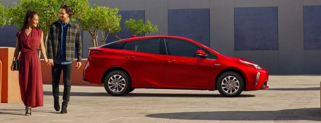 A man and a woman walking in front of a red 2022 Toyota Prius.