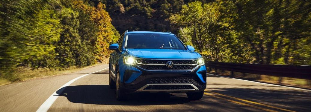 Blue 2022 Volkswagen Taos cruising on a leafy road