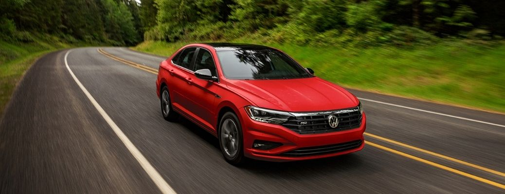 front and side view of the 2021 VW Jetta on a road with trees on either side