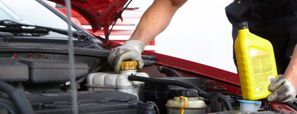 a technician changing oil in a car