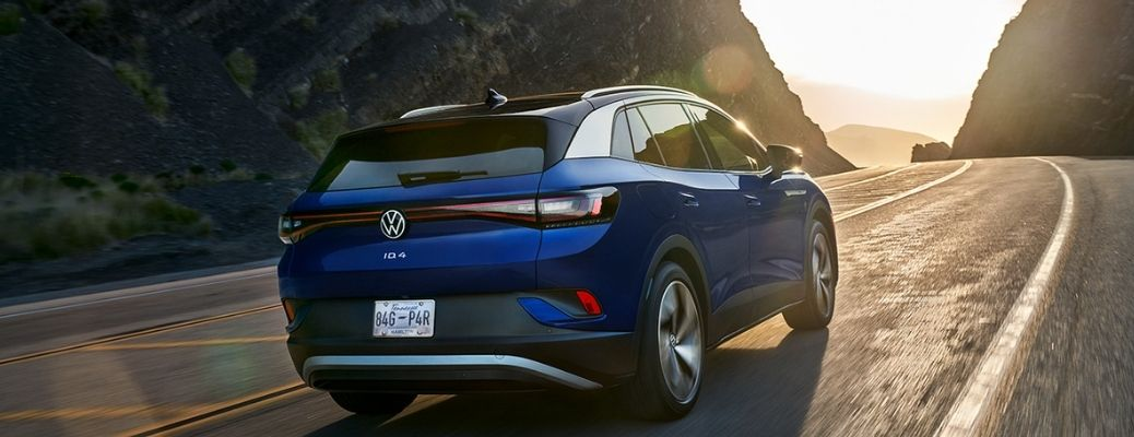 rear view of the 2021 VW ID.4 driving away on a road with mountains on either side