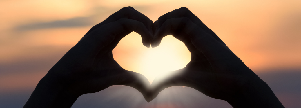 Two hands making a heart over a setting sun