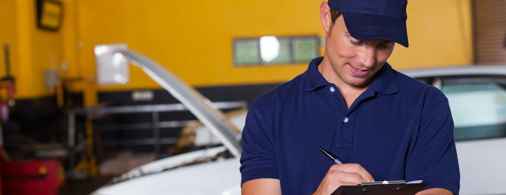 Car mechanic writing on clipboard by vehicle