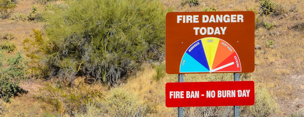 Fire danger sign with colored chart and arrow pointing to red