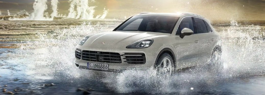 Front driver angle of a white 2021 Porsche Cayenne Coupe driving through shallow water