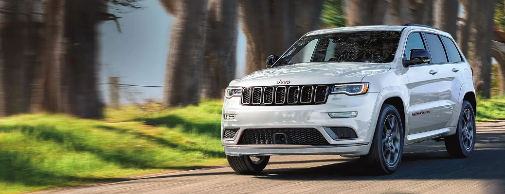 2021 Jeep Grand Cherokee drives along tree-lined road by water