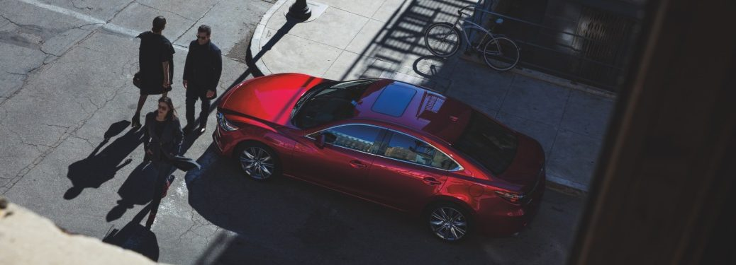 People walking in front of 2019 Mazda6