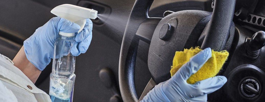 A stock photo of a person cleaning the inside of a vehicle.