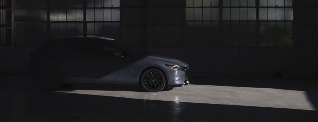 A silhouetted photo of the 2021 Mazda3 in a garage.