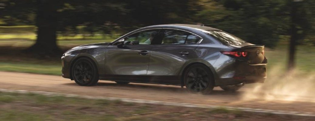 A left profile photo of the 2021 Mazda3 Sedan driving on a dirt road.