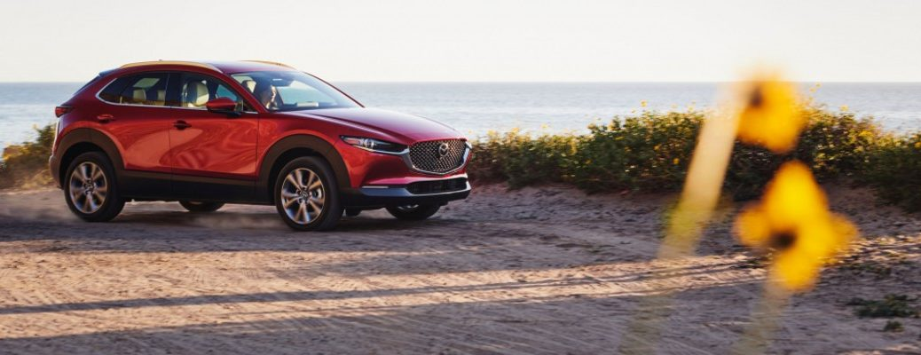 A photo of the 2021 Mazda CX-30 parked on a gravel road near an oceanside cliff.