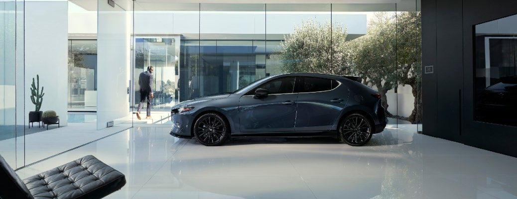 A left profile photo of the 2021 Mazda3 Hatchback parked in someone's living room.
