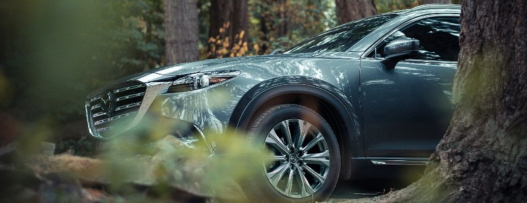 A Mazda crossover SUV parked in the woods.