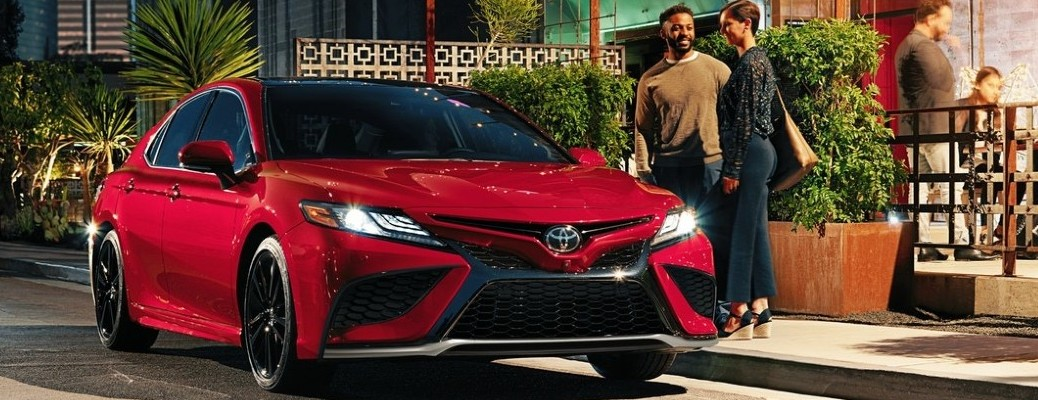 Happy couple standing next to 2021 Toyota Camry