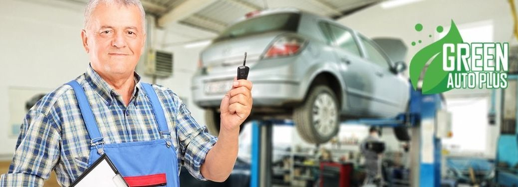 Mechanic Holding Key and Smiling in a Garage with Green Auto Plus Logo