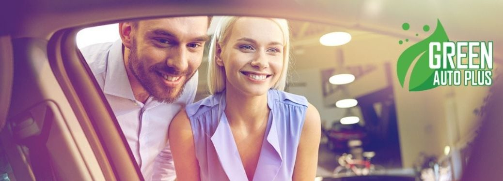 Couple Looking in the Window of a New Car with Green Auto Plus Logo