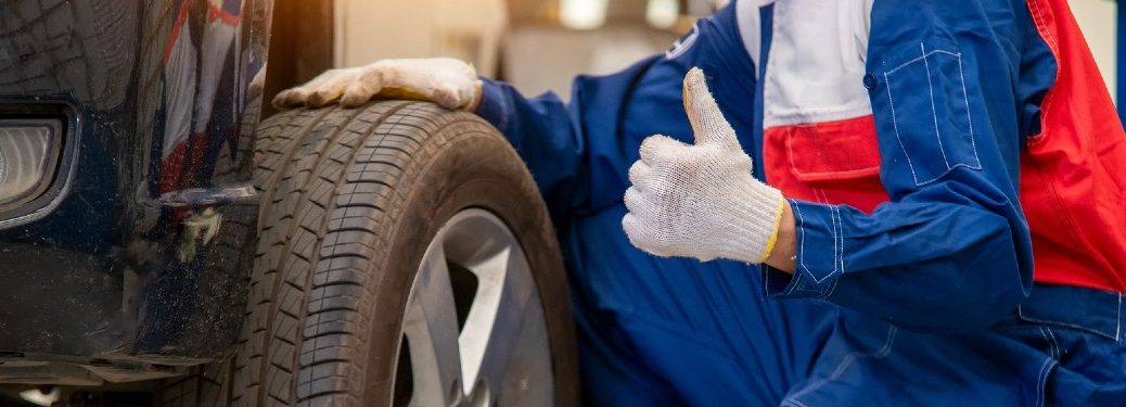 Mechanic giving a thumbs up next to a tire