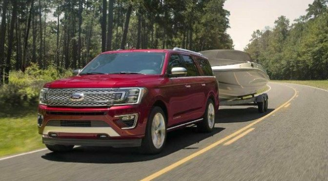 2018 Ford Expedition Towing a Boat Down a Highway