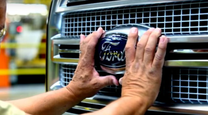 Production Worker Installing the Ford Badge on the Grille of a Ford F-150