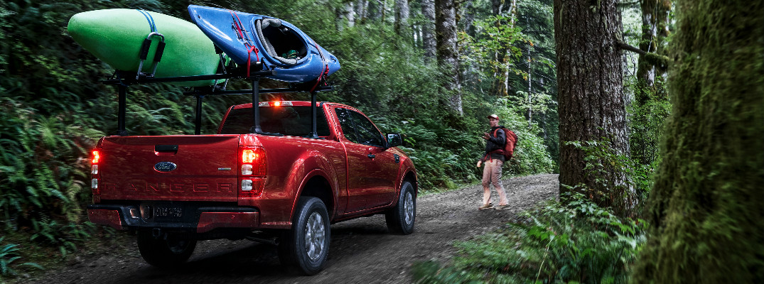 Red 2019 Ford Ranger carrying kayaks through a forest