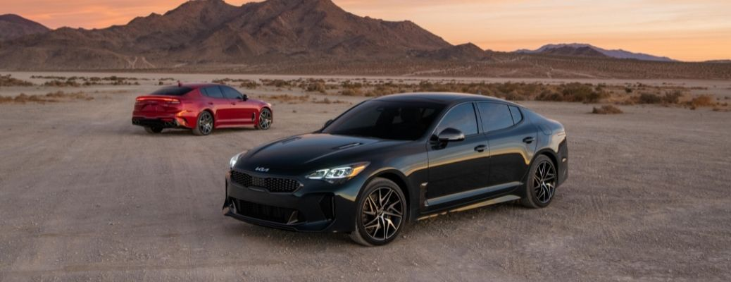 Two 2022 Kia Stinger GT-Line parked in front of a hill