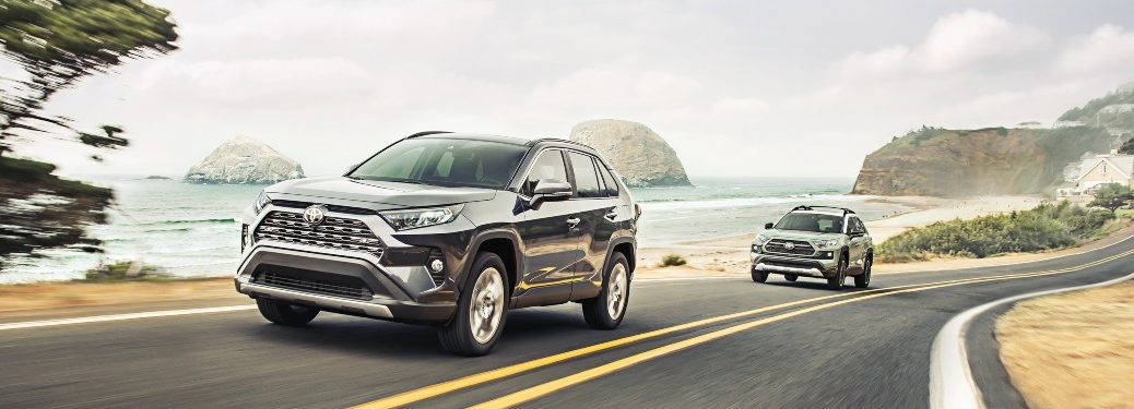 2021 Toyota RAV4 models driving past one another on a beachside road