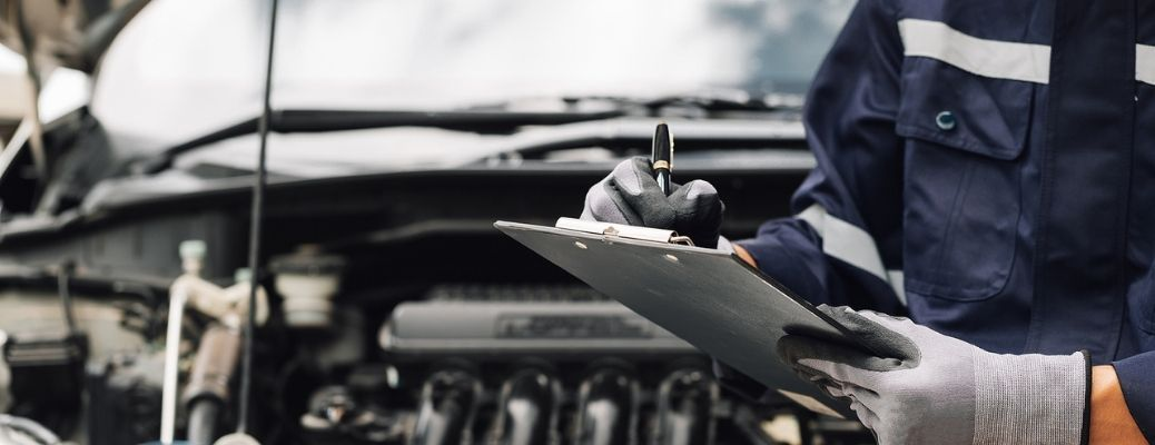 A mechanic holding a checklist while working on a car.
