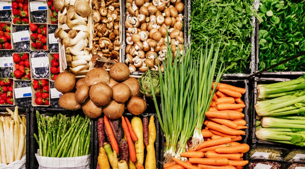 An aerial view of various vegetables, including mushrooms, carrots and asparagus at a local supermarket.