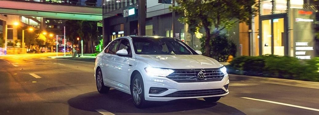 A white 2021 VW Jetta driving on the city street.