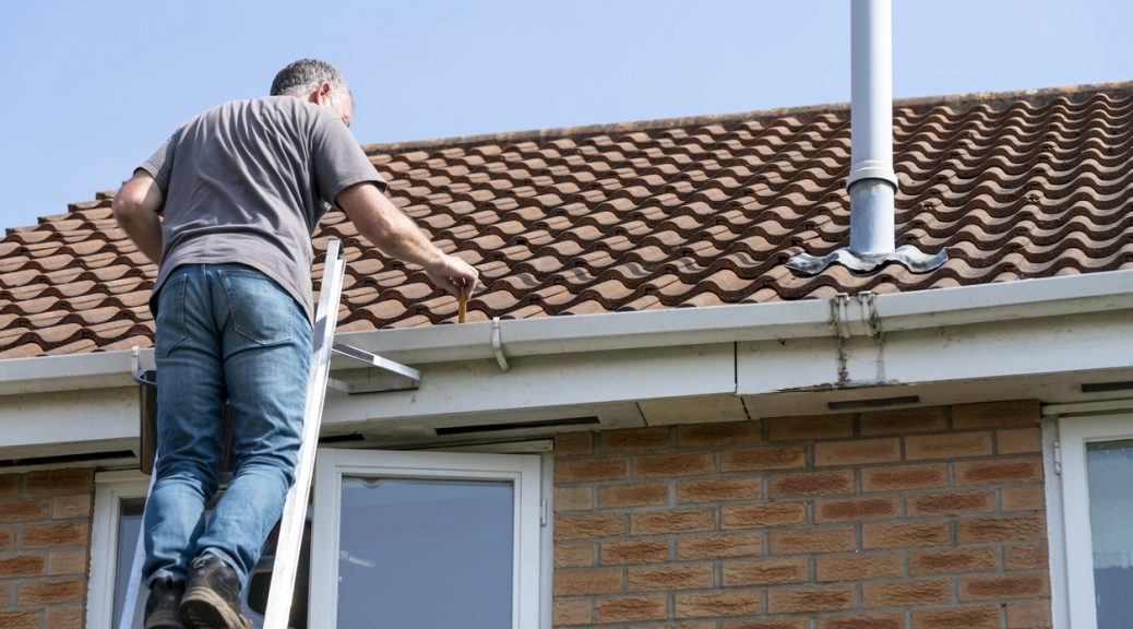 Senior man cleaning gutters on a suburban house.