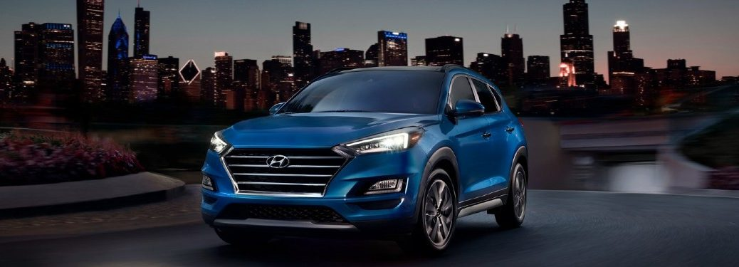blue 2021 Hyundai Tucson front fascia driver side parked at night in front of Chicago skyline