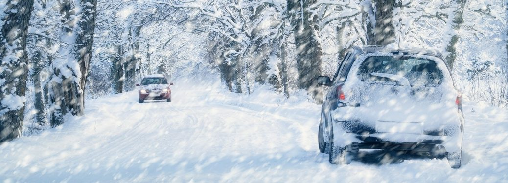 two vehicles driving in winter snow storm