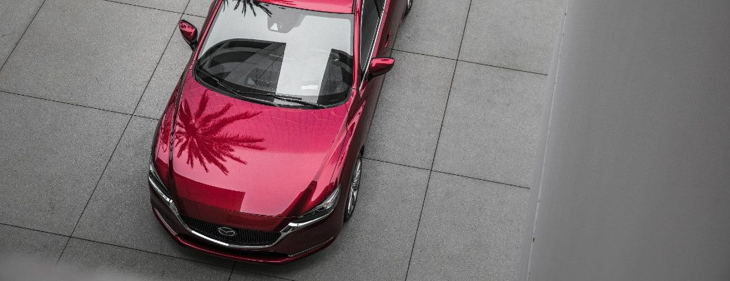 2018 and 2019 Mazda6 Sedan build overhead exterior shot with red paint color and trees reflecting off its design